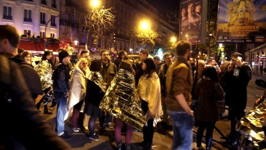 People warm up under protective thermal blankets as they gather on a street near the Bataclan concert hall following fatal attacks in Paris, France, November 14, 2015. Gunmen and bombers attacked busy restaurants, bars and a concert hall at locations around Paris on Friday evening, killing dozens of people in what a shaken French President described as an unprecedented terrorist attack   REUTERS/Philippe Wojazer